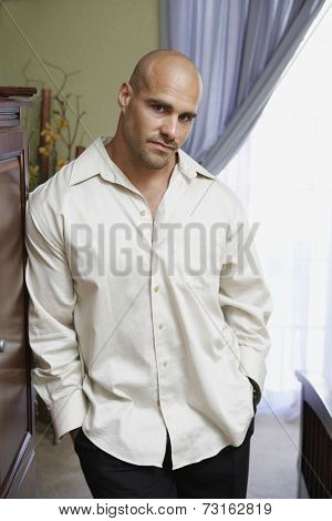 Man with hands in pockets leaning against furniture