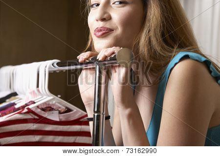 Hispanic woman leaning on rack of clothing
