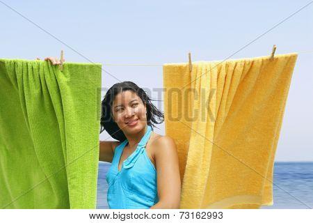 Hispanic woman hanging towels at beach