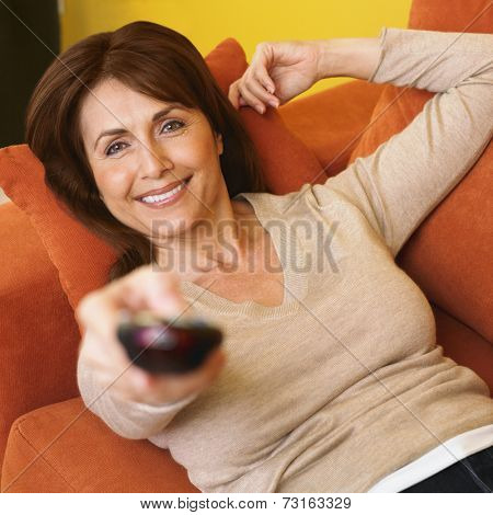 Hispanic woman pointing remote control