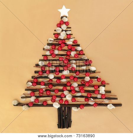 Abstract christmas tree design with red bauble decoration, pussy willow twigs and star over gold paper background.