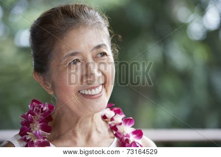 Senior Asian woman wearing lei