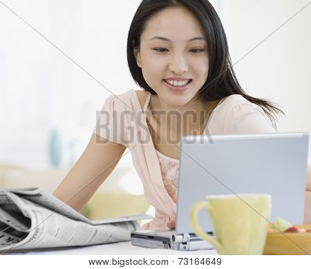 Asian woman looking at laptop