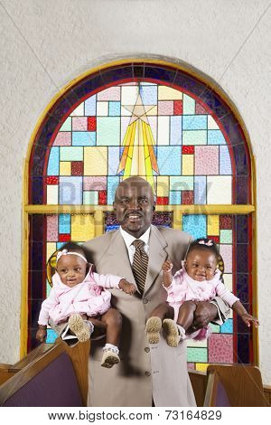 African American father holding babies in church