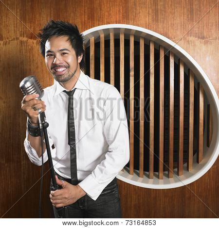 Asian man standing at microphone