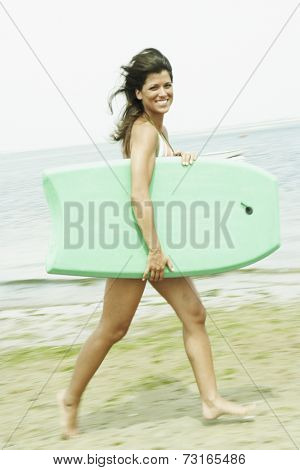 Woman carrying boogie board at beach
