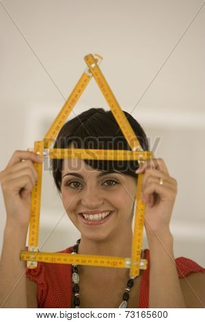 Woman holding folding ruler shaped like house
