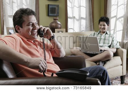 Hispanic father and son relaxing in livingroom