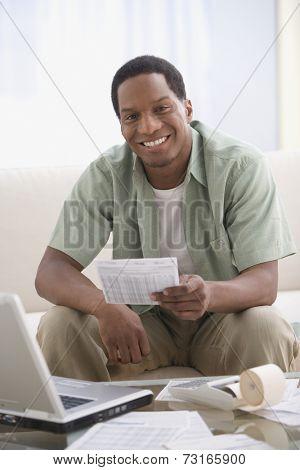 African American man paying bills