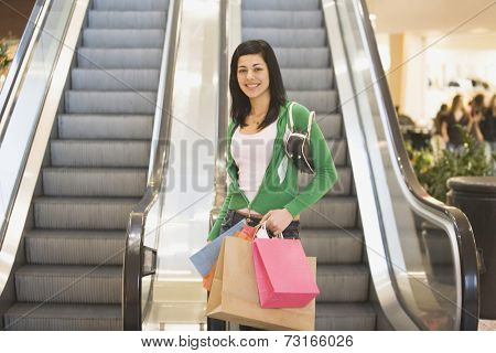 Hispanic teenage girl holding shopping bags
