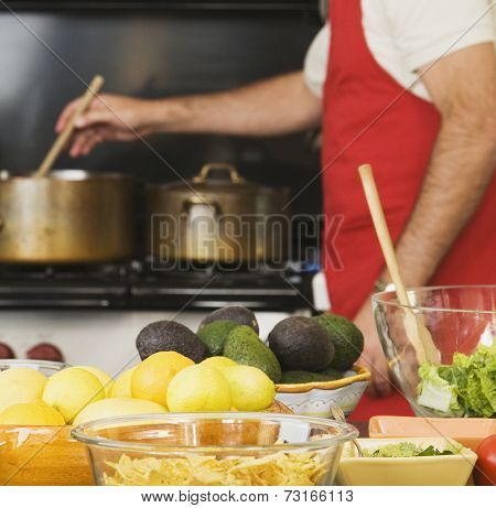 Food on counter in front of man cooking