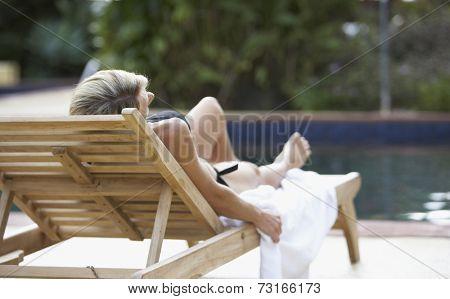Woman sunbathing next to swimming pool
