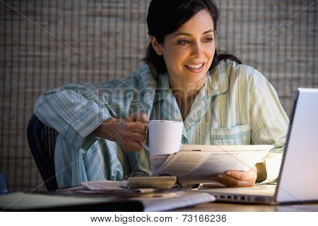 Hispanic businesswoman working in pajamas