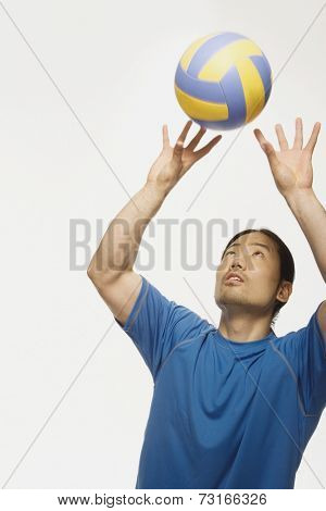 Asian man bouncing volleyball