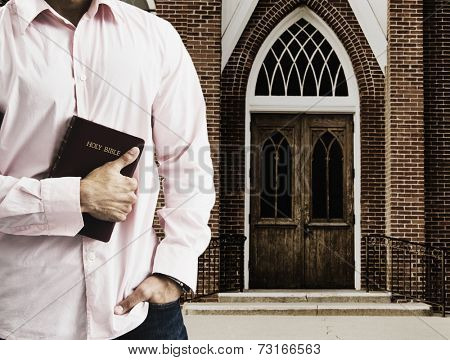Mixed Race man holding the bible in front of church