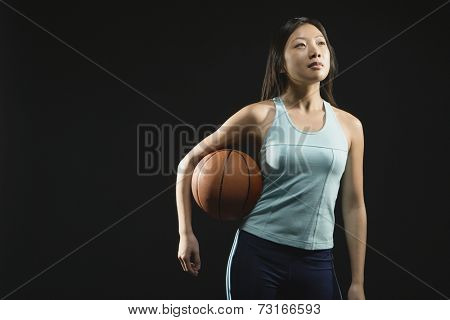 Asian woman holding basketball