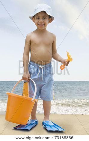 Hispanic boy with pail and shovel at beach