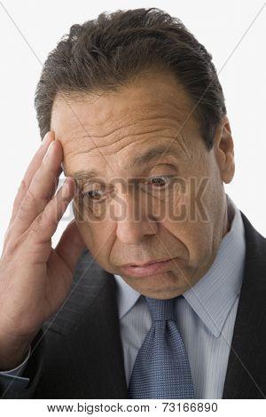 Hispanic businessman with hand on head