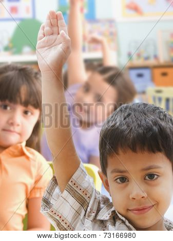 Hispanic boy raising hand in class