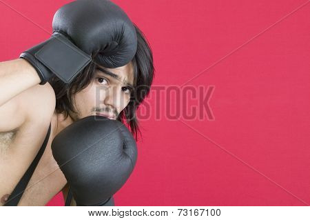 Young Hispanic man wearing boxing gloves