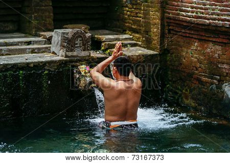 SEPTEMBER 18, 2014 - BALI, INDONESIA: Devotee bathes in the temple pool of Pura Tirta Empul in a cleansing and purification ceremony. Hinduism is the religion of the Balinese people.