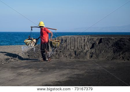 SEPTEMBER 18, 2014 - BALI, INDONESIA: A worker in the pours sea water onto the sand to saturate it with salt, and latter purification processes will extract out the salt crystals.
