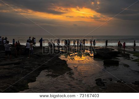 SEPTEMBER 17, 2014, BALI, INDONESIA: Tourists view the spectacular sunset on Bali Island, Indonesia. Bali Island is an important tourist destination in the world.
