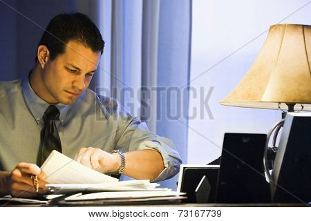 Hispanic businessman checking watch