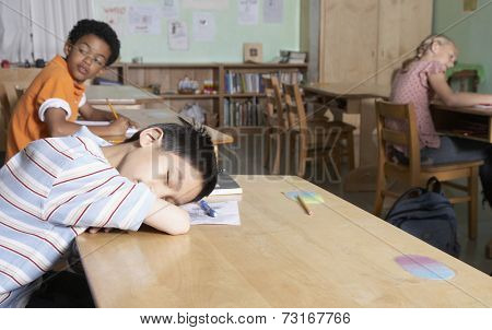 Asian boy sleeping in classroom