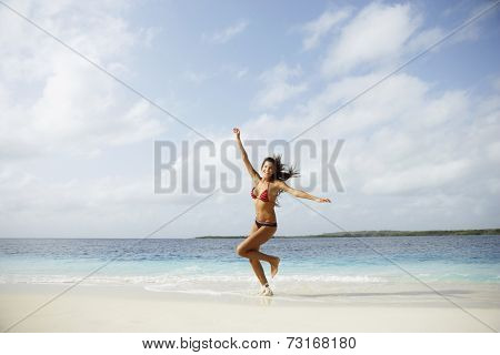 South American woman running on beach