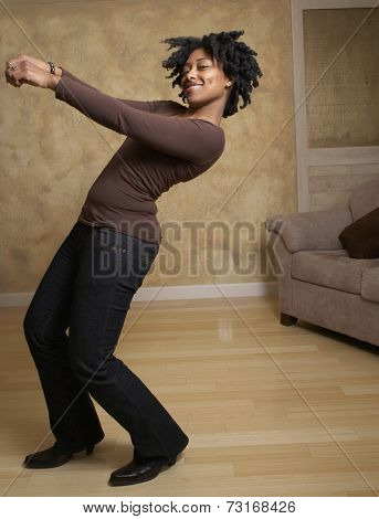African woman dancing in livingroom