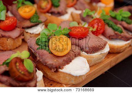 Bruschettas with beefsteak and pesto sauce, close-up
