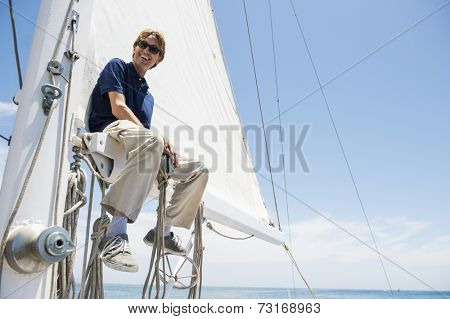 Low angle view of smiling man sitting on yacht boom