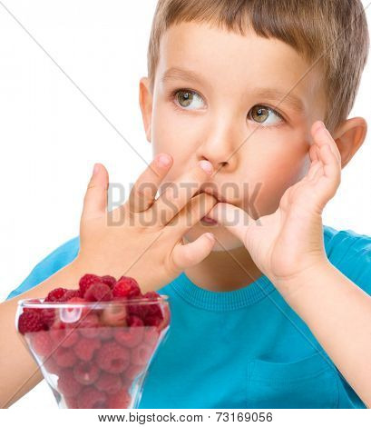 Little boy is eating raspberries, isolated over white