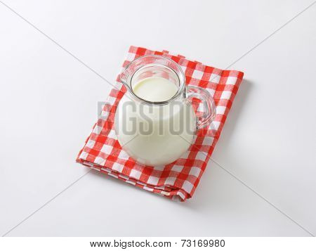 liter of organic milk in the glass pitcher, standing on the fabric dishtowel