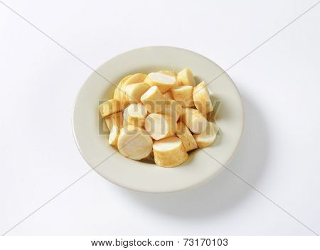 plate of sliced parsley root on white background