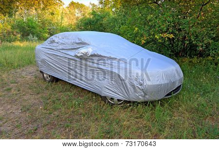 car with cover in forest meadow
