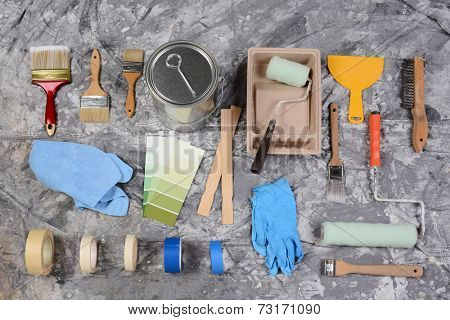 High angle shot of the tools needed to paint spread out on a drop cloth. Items include, paint can, brushes, rollers, tray, tape, color chart, rags, wood stir sticks, scrapers and latex gloves.