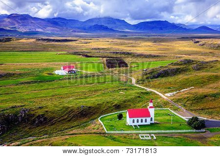 View to a small church and a farm from Helgafell Mountain in western Iceland