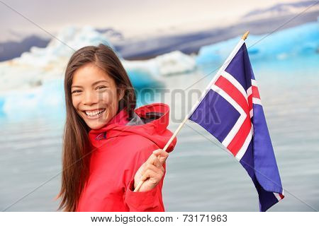 Icelandic flag - girl holding Iceland flag at glacier lagoon / glacial lake Jokulsarlon. Happy smiling woman tourist in front of iceberg.