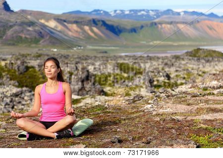 Meditating yoga woman in meditation in nature. Female model relaxing in serene harmony in lotus position pose. Healthy wellness lifestyle image with multicultural young woman. Image from Iceland.