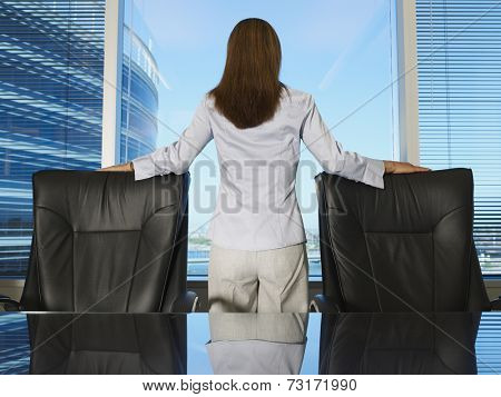 Hispanic businesswoman looking out window
