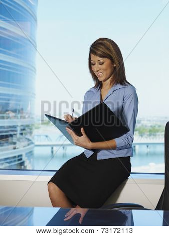 Hispanic businesswoman writing in folder