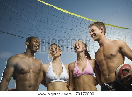 Multi-ethnic friends under beach volleyball net