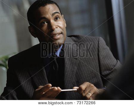 African American businessman holding pen