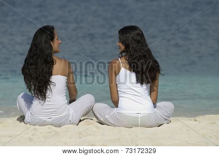 Hispanic women sitting on beach