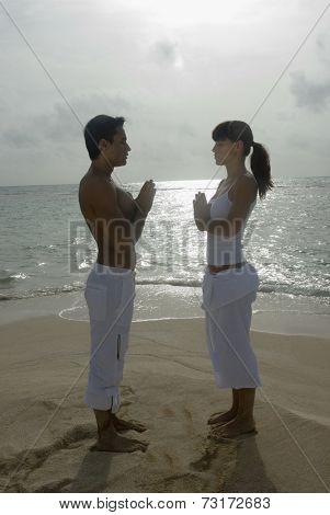 Multi-ethnic couple practicing yoga on beach