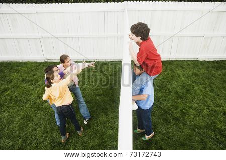 Mixed Race boys looking over fence at girls
