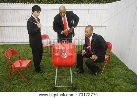 Multi-ethnic businessmen looking at barbeque