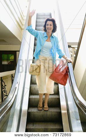 Hispanic woman waving on escalator